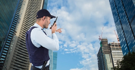 Digital composite of Security guard talking on walkie talkie and gesturing while standing by buildings against sky Stock Photo