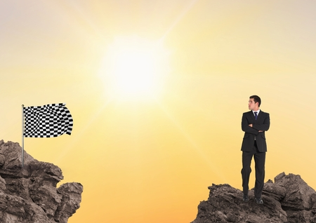 Digital composite of Businessman looking at checkered flag while standing on rocks against sky