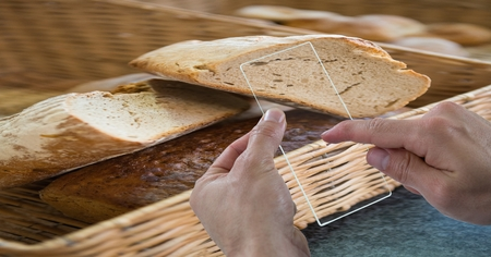 Digital composite of Cropped hands taking picture of bread through transparent device at cafe