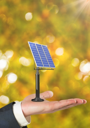 Digital composite of Cropped hand holding solar panel against defocused background
