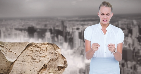 Digital composite of Digital image of angry businesswoman standing by rock against city
