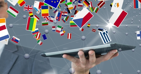 camaraderie: Digital composite of Digital image of businessman holding digital tablet with various flags and connecting dots