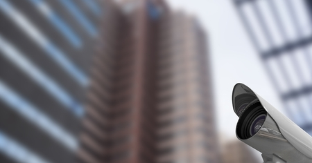 Digital composite of CCTV camera on road against buildings Stock Photo
