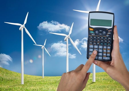 Digital composite of Hands holding calculator on wind farm against sky