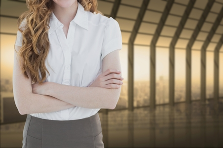Digital composite of business woman with arm cross in a corridor Stock Photo