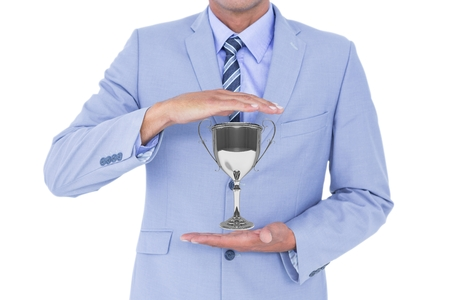 Digital composite of Business man holding a trophy in his hands against white background Stock Photo
