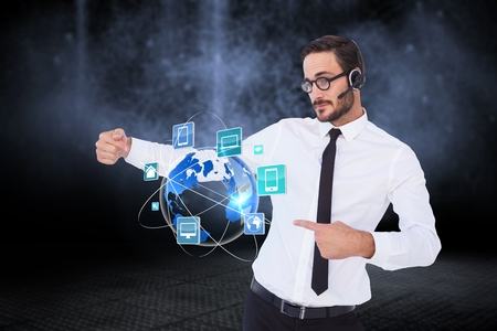 Digital composite of Business man presenting icons and wearing Headset Stock Photo