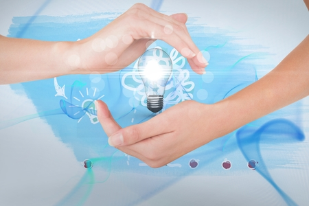 Digital composite of Hands holding bulb against blue background Stock Photo - 79323681