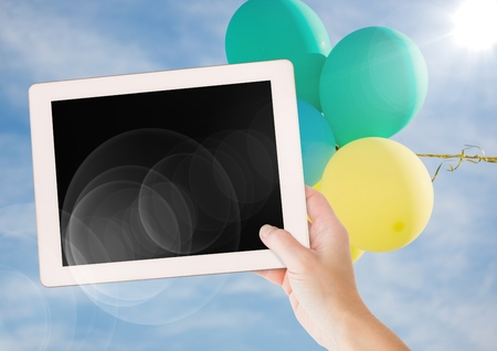 Digital composite of Hand with tablet against sky and balloon with flares