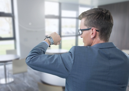 round chairs: Digital composite of Businessman holding arm with watch to eyes in office