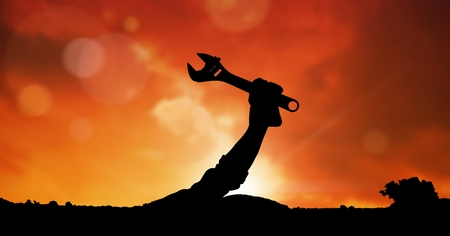 Digital composite of Silhouette hand holding spanner against sky during sunset Stock Photo