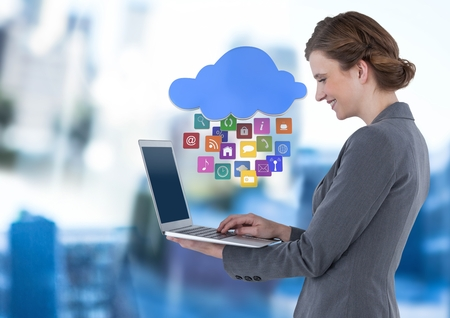 classy house: Digital composite of Businesswoman holding laptop with cloud apps icons in blue motion public space Stock Photo