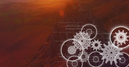Digital composite of White gear graphics against mountain rock in sunset Stock Photo
