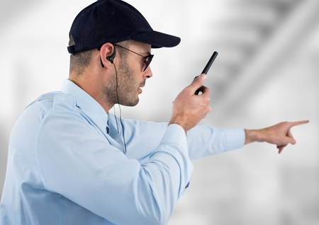 Digital composite of security guard with headphones and speaking with the walkie-talkie. Light blurred background