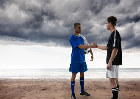Digital composite of soccer players in the beach giving the hands with clouds on the sky