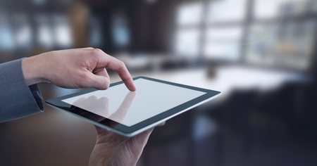 Digital composite of Businessman touching tablet in wide room towards windows Stock Photo