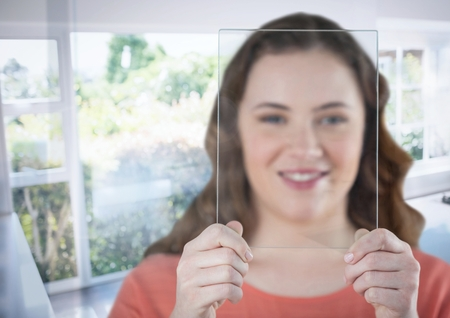 Digital composite of Woman holding glass screen by sunny window Stock Photo