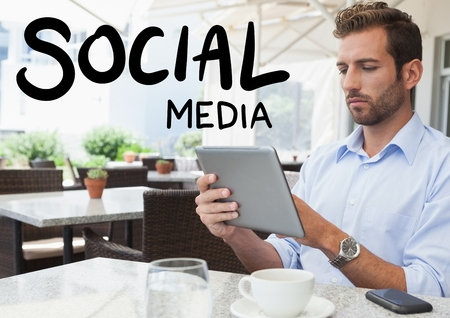 Digital composite of Social media text against man in cafe with tablet Imagens