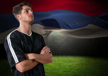 Digital composite of soccer player looking up in the field, with a flag behind