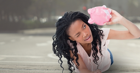 asphalt texture: Digital composite of Broke black woman looking on piggy-bank to emphases the empty pocket concept with a basket field in the background