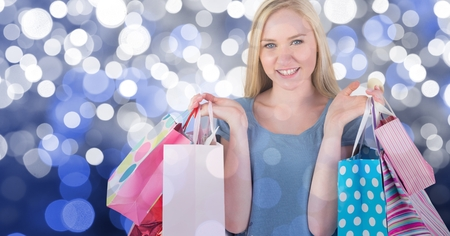 Woman holding shopping bags against blue glowing background Stock Photo