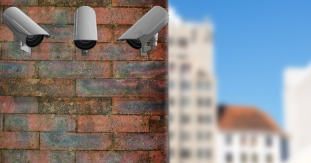 Digital composite of 3 CCTV on a brick wall with a blurred city in the background