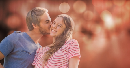 Digital composite of a happy couple kissing against orange glowing background