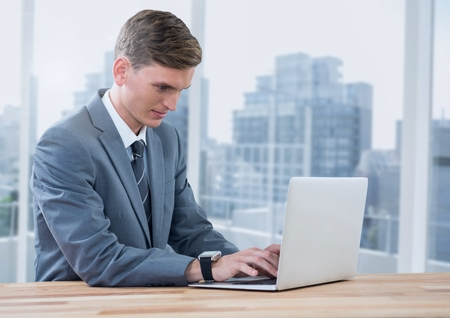Digital composite of Businessman on laptop against windows with city
