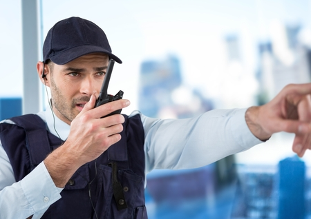 Digital composite of Security guard with walkie talkie pointing against blurry window showing city