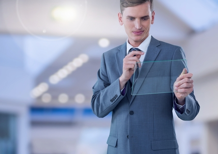 Digital composite of Businessman holding glass screen in large bright space