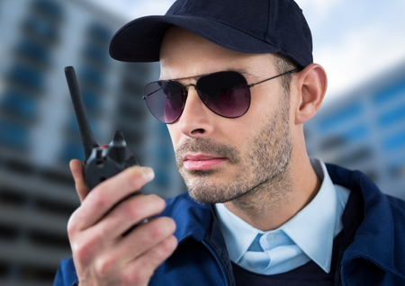 Digital composite of serious security guard with glasses and walkie-talkie with a blurred building background Stock Photo