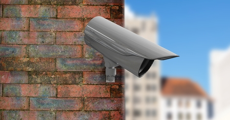 Digital composite of CCTV on a brick wall with the city in the foreground Stock Photo