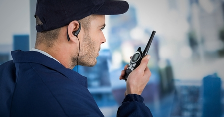 Digital composite of Security guard with cap and walkie talkie against blurry window showing city Stock Photo
