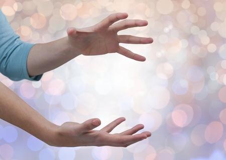erratic: Digital composite of Hands open erratic with sparkling light bokeh background