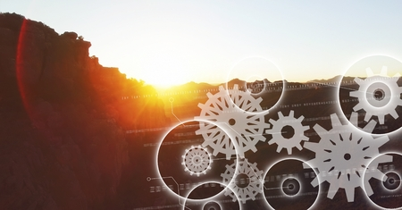 Digital composite of White gear graphics against mountain and sunset