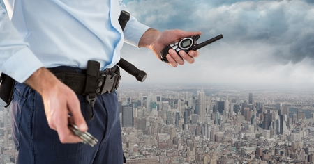 Digital composite of Security guard lower body with walkie talkie against skyline and clouds