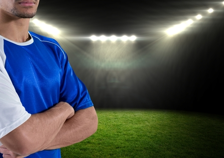 business pitch: Digital composite of soccer player with his hands folded and with blue t-shirt in the field at night with lights Stock Photo