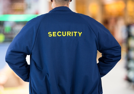 Digital composite of security guard back in lights background