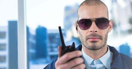 Digital composite of Security guard with walkie talkie against blurry window showing city