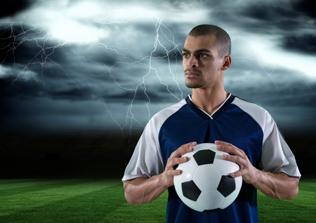 Digital composite of soccer player with ball on his hand in the field. storm