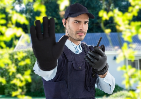 Digital composite of security guard with hat, headphone and walkie-talkie, saying stop with his hand in front of the house