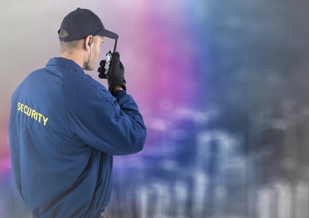 baton: Digital composite of Back of security guard with walkie talkie against blurry wall with city sketch
