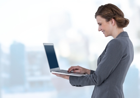 Digital composite of Businesswoman holding laptop in bright blue motion public space