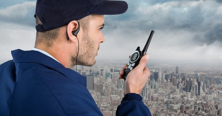 earpiece: Digital composite of Security guard with cap and walkie talkie against skyline and clouds Stock Photo