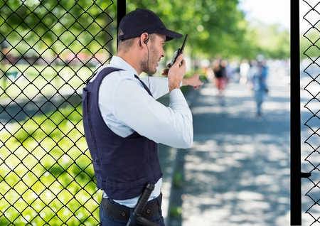 earpiece: Digital composite of security guard of the park spiking with the walkie-talkie and point to something. Stock Photo