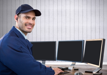 earpiece: Digital composite of security guard smiling in front of the computers with white wood background