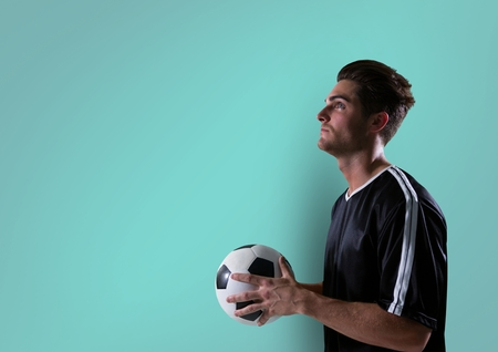 Digital composite of soccer player looking up with ball on hands. blue background
