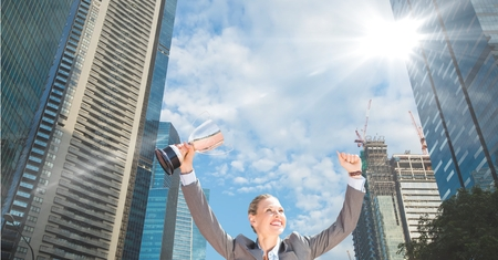 Digital composite of businesswoman with trophy in her hand. In te city