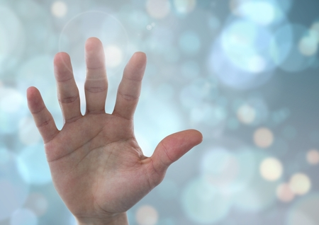 Digital composite of Hand open with sparkling light bokeh background