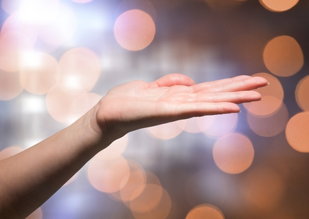 freely: Digital composite of Hand open freely with sparkling light bokeh background